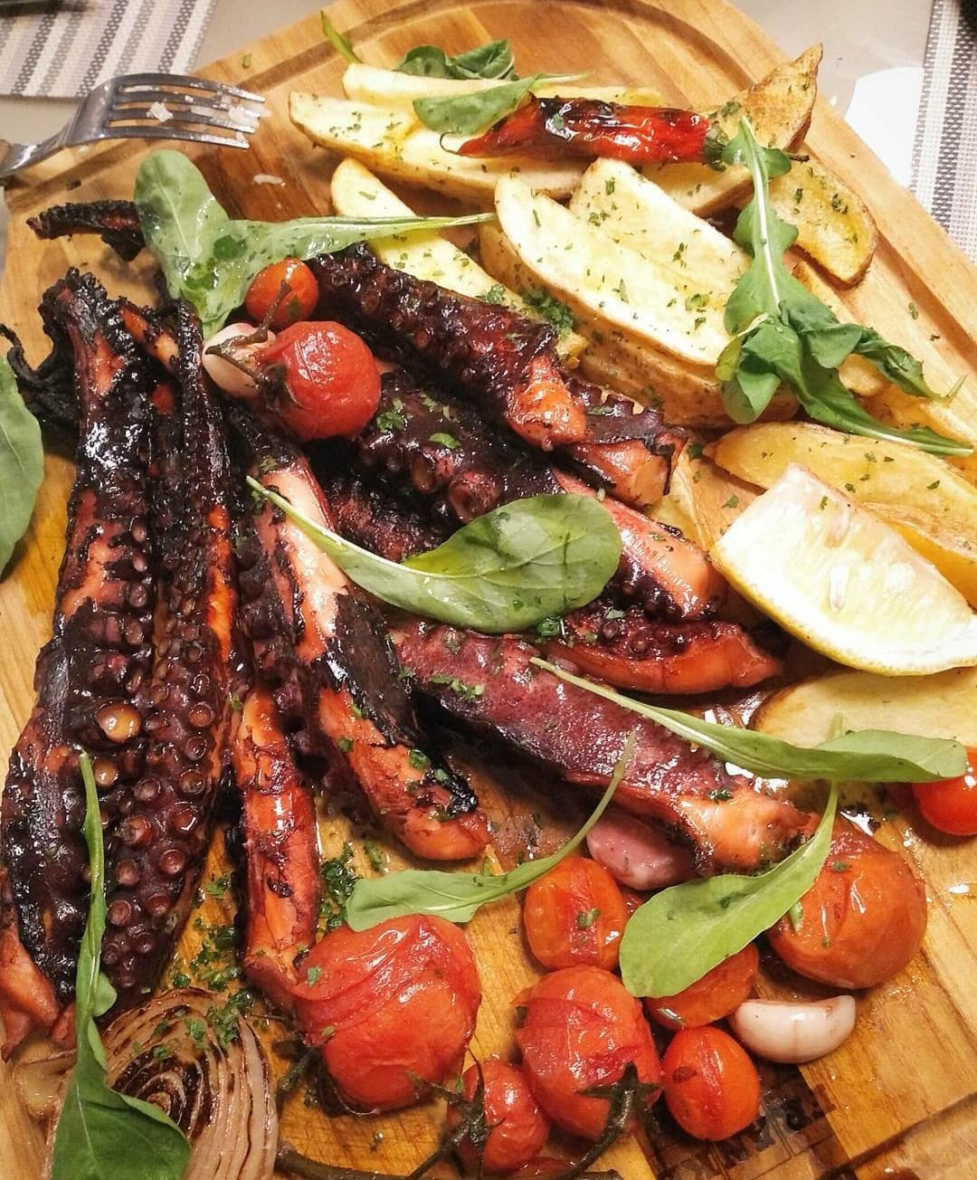 Polvo na Brasa servido tomates assados e batatas rústicas